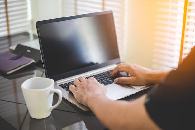 L'uomo di affari che lavora al computer portatile, giovane utilizza la tecnologia