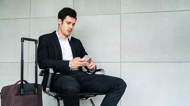 L'uomo di affari sta sedendosi sulla sedia che aspetta il viaggio di viaggio d'affari con la valigia e la chiamata dello smartphone