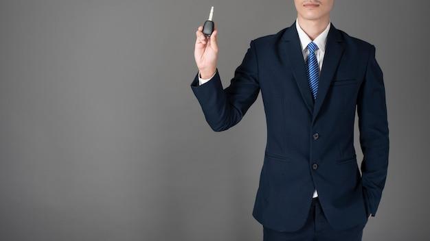 L'uomo di affari sta tenendo la chiave dell'automobile, fondo grigio in studio