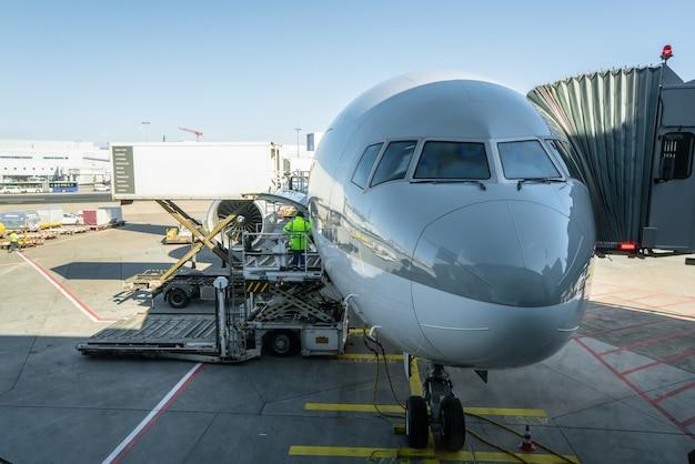 L'uomo di carico sulla piattaforma di carico carica il trasporto aereo verso gli aerei cargo.