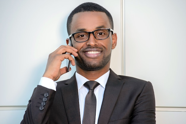 L'uomo di colore con gli occhiali parla al telefono.