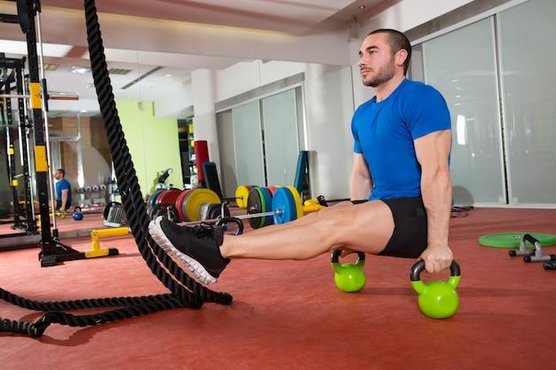 L'uomo di fitness crossfit l-sits kettlebells l si esercita