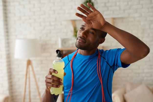 L'uomo di forma fisica con la bottiglia sta riposando dopo l'addestramento duro.