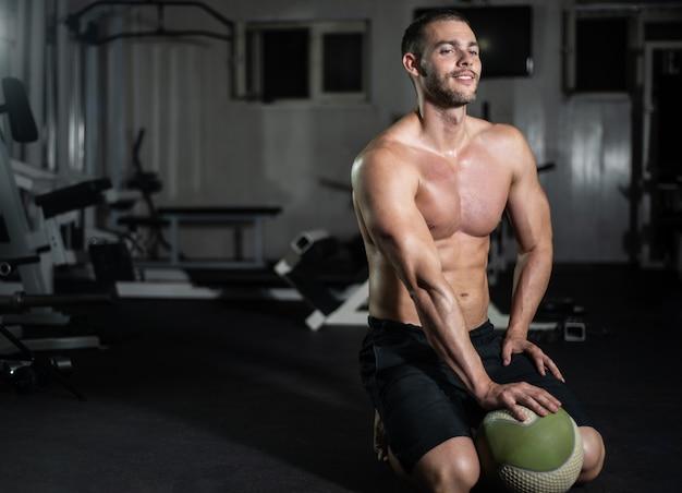 L'uomo di forma fisica posa con una palla in palestra