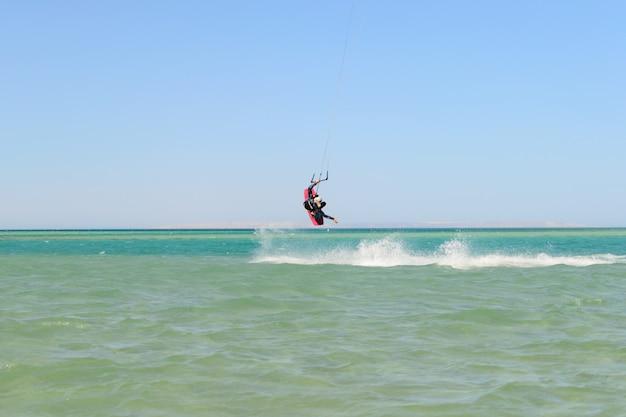 L'uomo di kitesurf salta sul mare