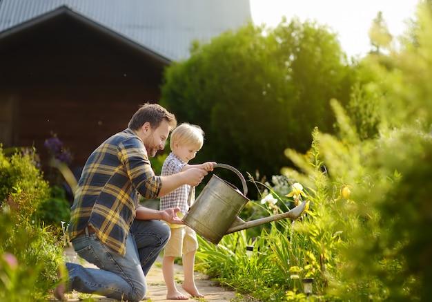L'uomo di medio evo ed il suo figlio piccolo che innaffiano i fiori nel giardino al giorno soleggiato dell'estate