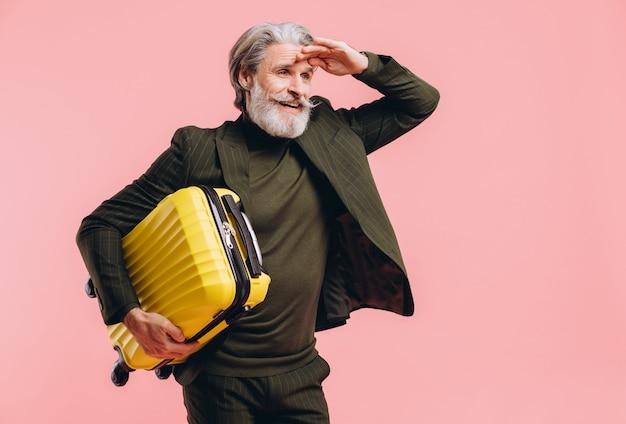L'uomo di mezza età barbuto dai capelli grigi in un vestito tiene una valigia gialla sul rosa