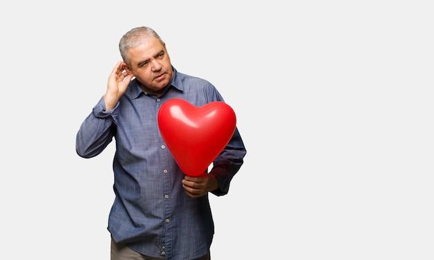 L'uomo di mezza età che celebra san valentino tenta di ascoltare un pettegolezzo