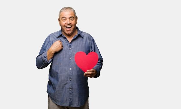 L'uomo di mezza età festeggia il giorno di san valentino sorpreso, si sente felice e prospero