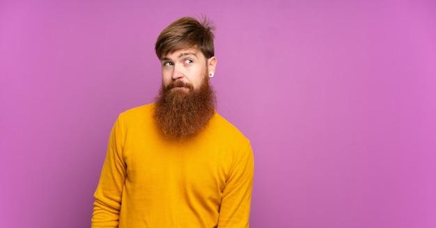 L'uomo di redhead con la barba lunga sopra la porpora isolata che fa i dubbi gesturing lo sguardo laterale