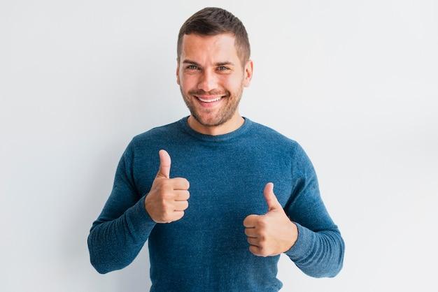 L'uomo di smiley dà il segno giusto alla macchina fotografica