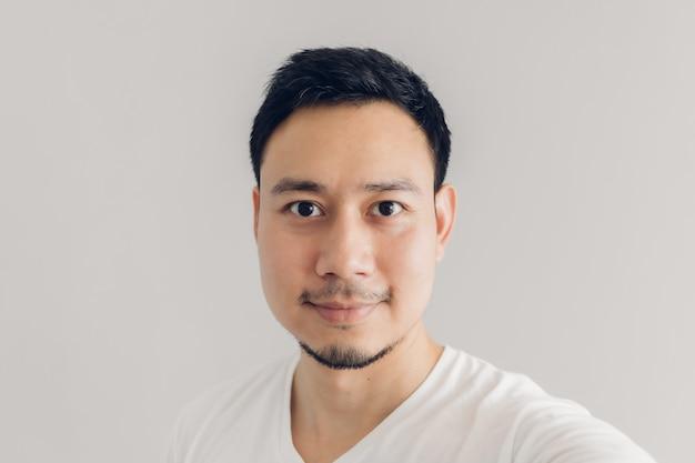 L'uomo di sorriso sta prendendo il selfie di se stesso con la maglietta bianca e il fondo grigio.