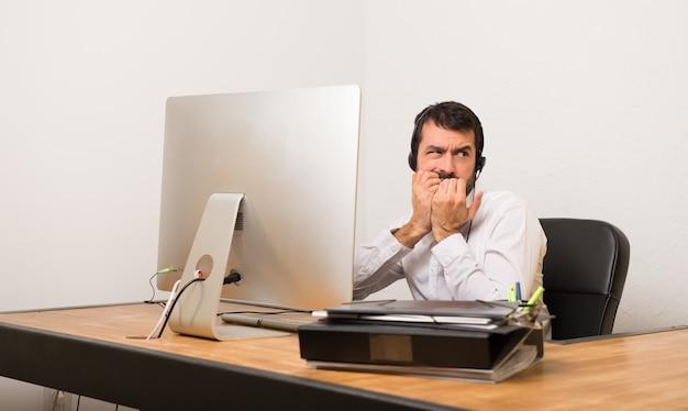 L'uomo di telemarketer in un ufficio è un po 'nervoso e spaventato a mettere le mani in bocca