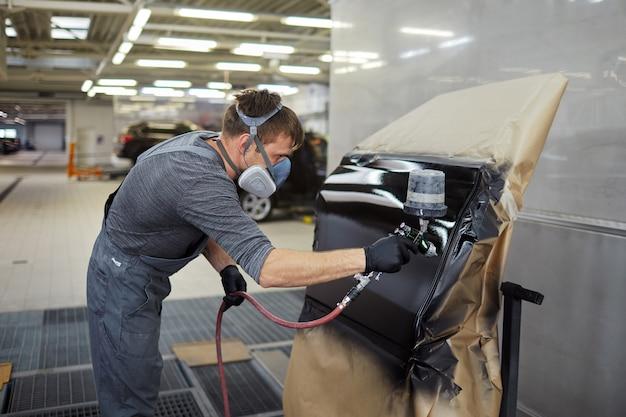 L'uomo dipinge parte da auto, riparazione, stazione di servizio, concessionaria auto