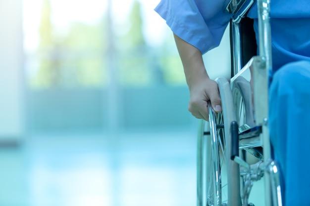 L'uomo disabile asiatico sta sedendosi in una sedia a rotelle. tiene le mani sul volante, eq medica