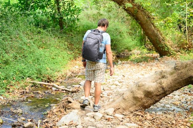 L'uomo durante un'escursione attraverso una gola di montagna supera gli ostacoli.