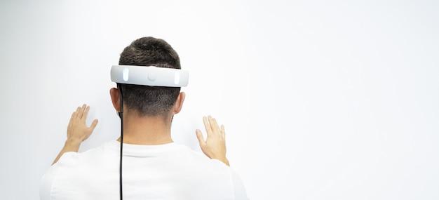 L'uomo è in piedi con la schiena in occhiali virtuali su uno sfondo bianco