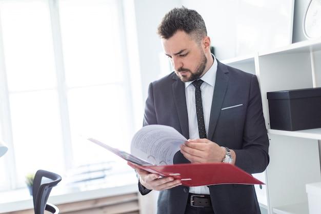 L'uomo è in piedi vicino al rack in ufficio e scorre la cartella con i documenti.