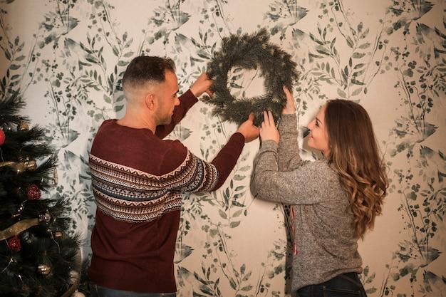 L'uomo e la donna allegra che appendono il natale si avvolgono vicino all'albero di abete decorato
