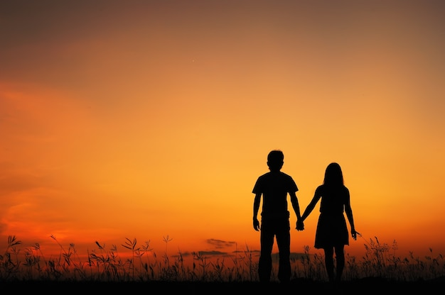 L'uomo e la donna amano nel tramonto