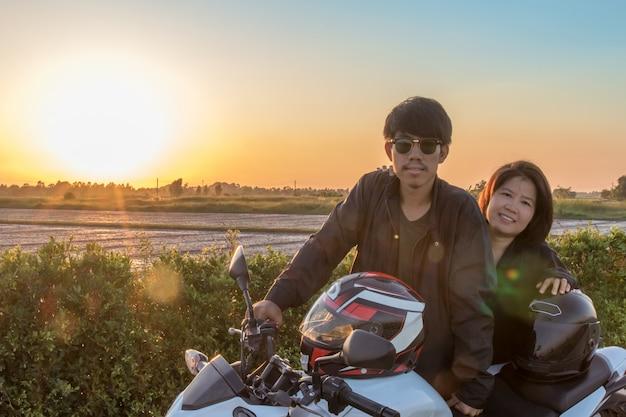 L'uomo e la donna asiatici con il casco e indossano e fissano prima di guidare la grande bici della bici sulla strada per la sicurezza