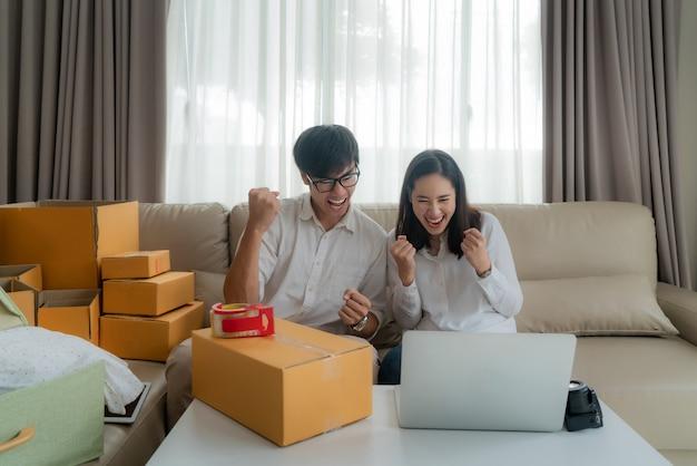 L'uomo e la donna asiatici vendono i loro online tramite il computer in casa e sono molto soddisfatti quando ci sono molti dei suoi ordini. avvio di piccola impresa imprenditore di pmi o concetto di libero professionista