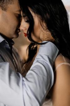 L'uomo e la donna attraenti si abbracciano tenere in piedi tenero nello studio