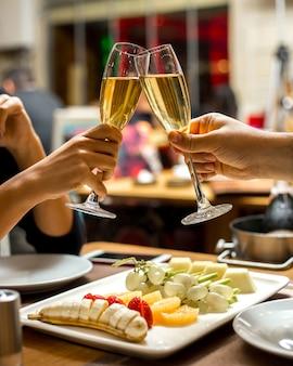L'uomo e la donna bevono champagne con la banana del piatto di frutta con le fragole e l'uva