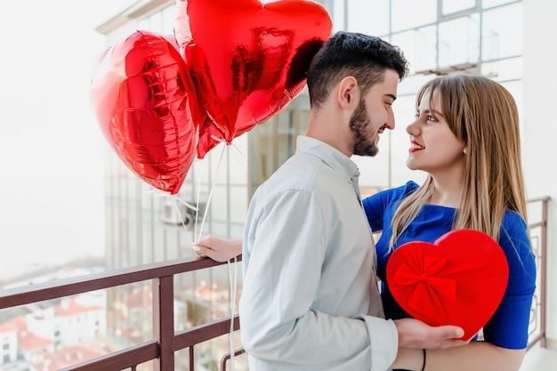 L'uomo e la donna con il regalo e il cuore rosso hanno modellato i palloni sul balcone a casa