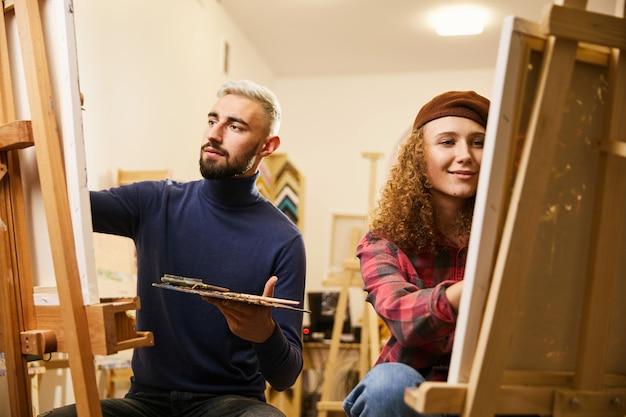 L'uomo e la donna disegnano dipinti su cavalletti