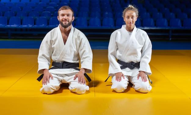 L'uomo e la donna in kimono bianco con una cintura nera si siedono sul pavimento e meditano nella palestra. arti marziali orientali, judo