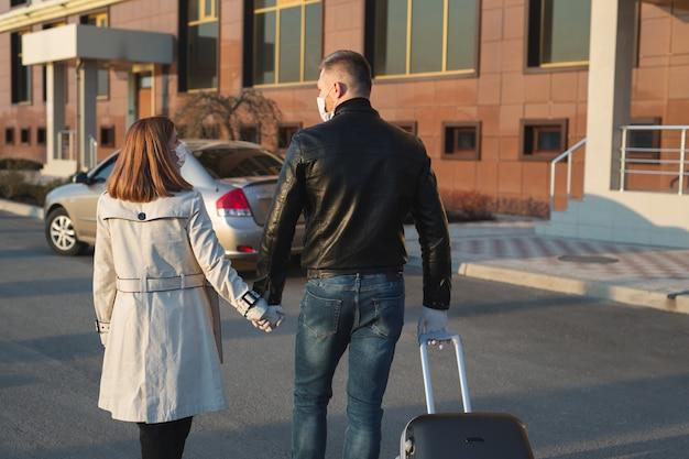 L'uomo e la donna in maschera protettiva e guanti medici con una valigia escono di casa in macchina durante la quarantena e l'autoisolamento. il coronavirus. covid 19.