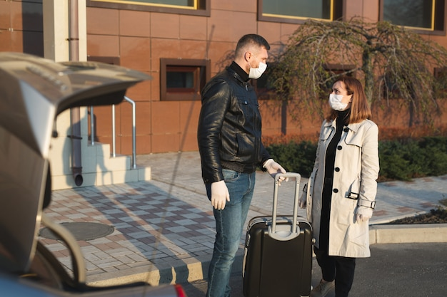 L'uomo e la donna in maschera protettiva medica e guanti con una valigia escono di casa