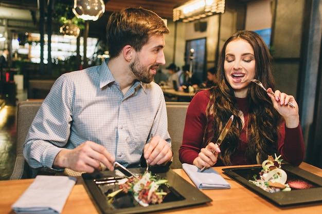 L'uomo e la donna mangiano al tavolo del ristorante e parlano tra loro. si stanno godendo l'un l'altro.
