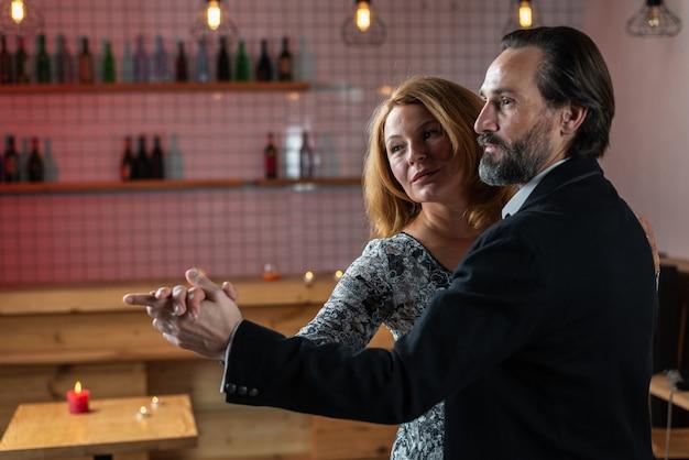 L'uomo e la donna si divertono ballando in un ristorante che guarda in una direzione insieme vicino
