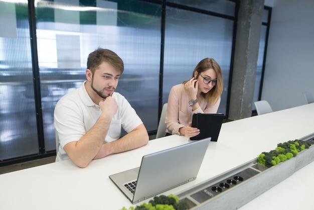 L'uomo e la donna si siedono con gadget al lavoro.
