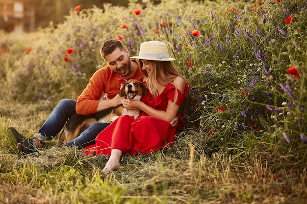 L'uomo e la donna si siedono con un divertente beagle sul campo verde con i papaveri rossi