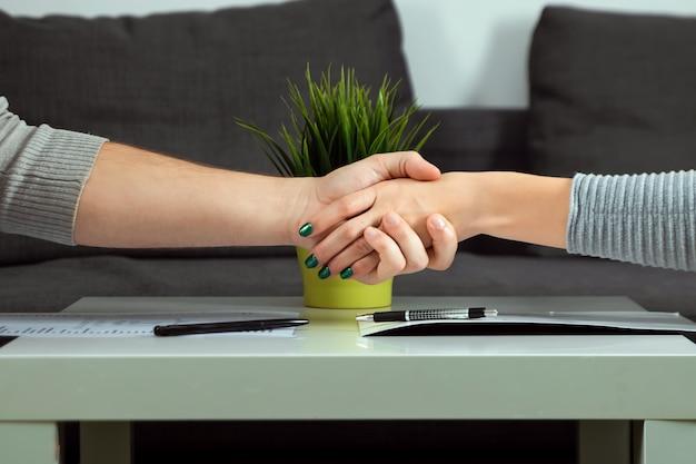 L'uomo e la donna stringono il primo piano delle mani