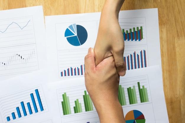 L'uomo e la scossa della femmina consegnano finanziario, grafico commerciale e diagramma