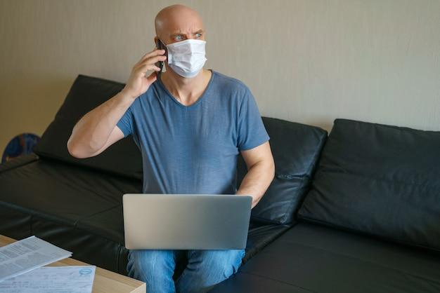 L'uomo è seduto su un divano in una maschera protettiva con un computer portatile e un telefono, lavoro a distanza in quarantena