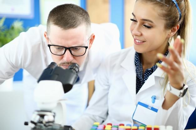 L'uomo e una donna guardano attraverso un microscopio in un laboratorio chimico