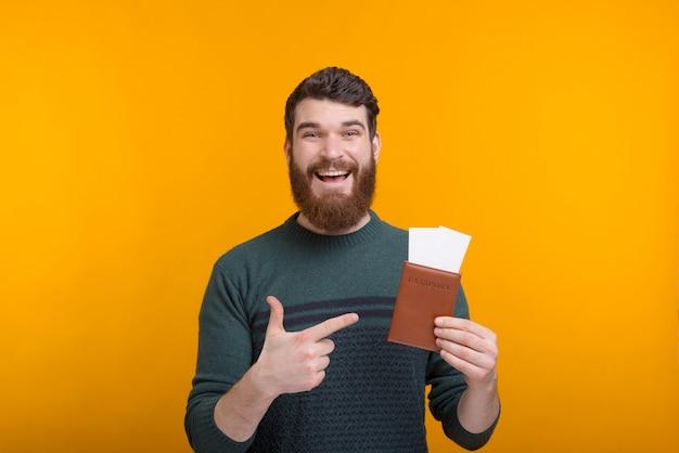L'uomo eccitato indica il passaporto e i biglietti che tiene.