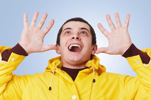 L'uomo eccitato sorridente allegro della brunetta indossa attivamente i gesti gialli della giacca a vento, guarda felicemente su, nota qualcosa di piacevole sul soffitto, isolato sopra la parete blu con lo spazio della copia per il vostro testo.