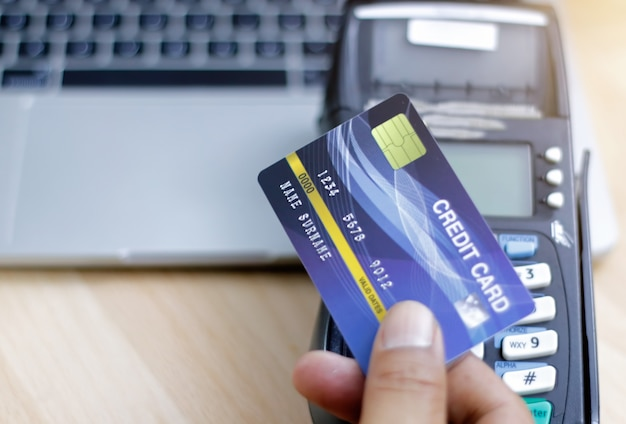 L'uomo effettua il pagamento con la carta di credito scorrendo attraverso il terminale. cliente che paga con la macchina di edc. acquistare e vendere prodotti o servizi