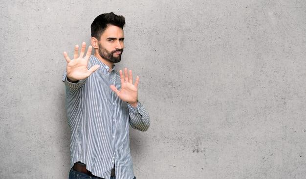 L'uomo elegante con la maglietta è un po 'nervoso e spaventato mentre allunga le mani verso la parte anteriore sulla parete strutturata