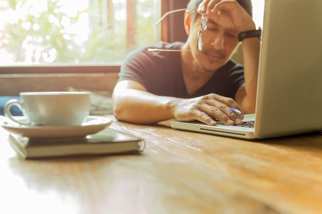 L'uomo esaurito che lavora al computer portatile con gli occhi si chiude contro la luce della finestra.