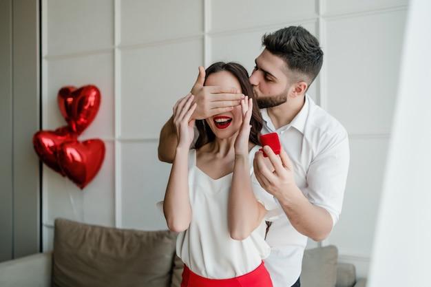 L'uomo fa una proposta a sorpresa alla donna con l'anello a casa con palloncini a forma di cuore sul divano in appartamento