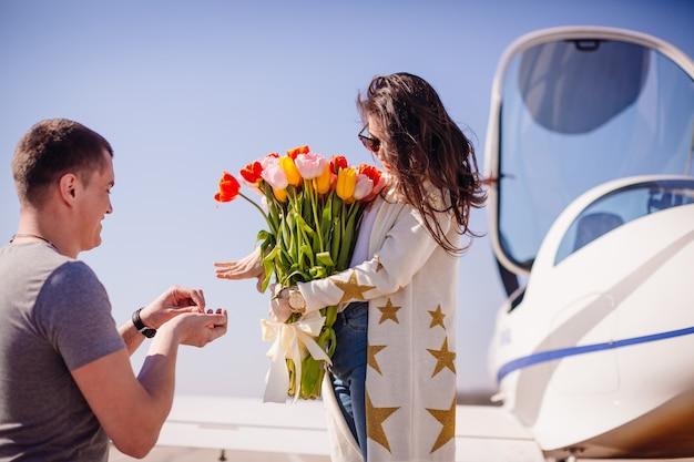L'uomo fa una proposta a una donna in piedi davanti a un aeroplano