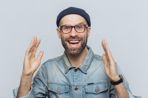 L'uomo felice bello alza le mani per l'eccitazione, ha un'espressione felicissima