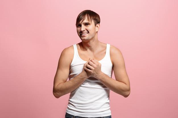 L'uomo felice che sta e che sorride contro lo spazio rosa.